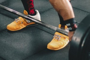 woman performing deadlift in reebok lifter shoes